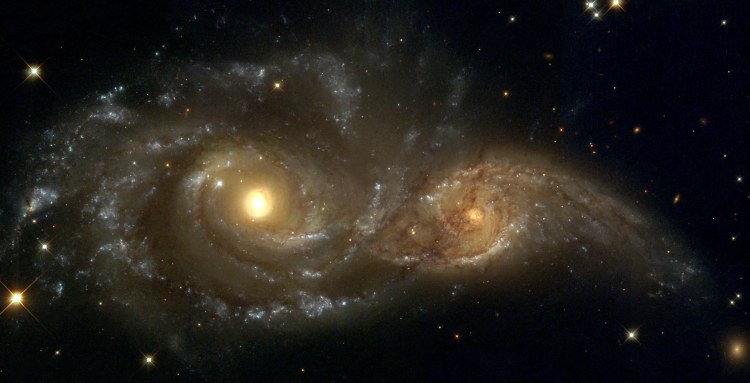 Spiral galaxies in collision: Billions of years from now, only one of these two galaxies will remain. Until then, spiral galaxies NGC 2207 and IC 2163 will slowly pull each other apart, creating tides of matter, sheets of shocked gas, lanes of dark dust, bursts of star formation, and streams of cast-away stars.