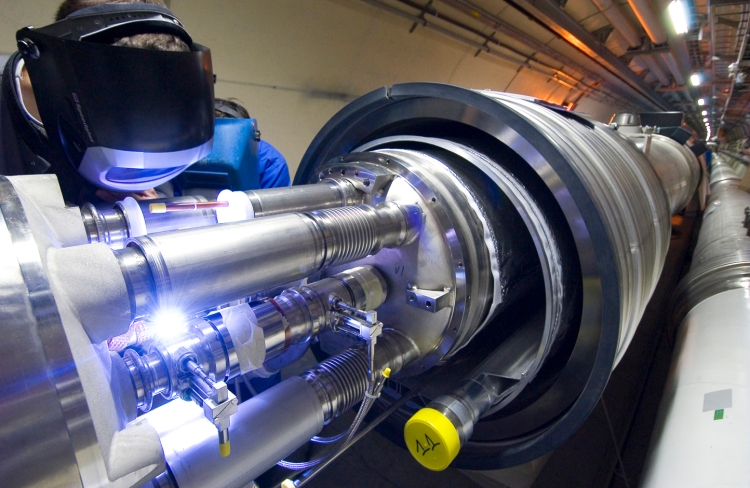 An engineer welds together the first cryomagnets for the Large Hadron Collider in 2005. 1,700 interconnections for the whole collider required 123,000 separate welding and assembly operations.